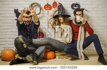 Halloween friends surprised drinking tea and celebrating. Holiday traditional symbols on white brick wall. Girl in witch hat. Men in casual wear sitting on floor. Friendship and people concept.