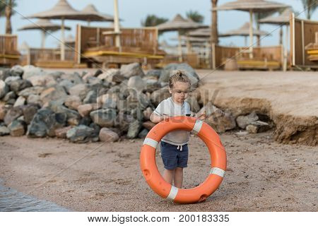 Kid small boy with adorable face long blond hair in blue shorts and white shirt holding orange ring saver at coast on background of sunbeds sun umbrellas and stones