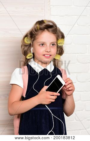 Child with headset and phone. Education and childhood. Kid choose career and listen music. Small girl with curler in hair.