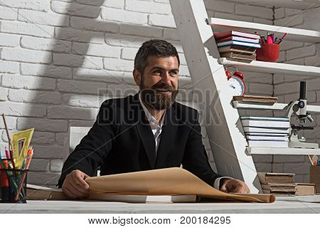 Alternative education and knowledge concept. Professor with happy face expression sits at desk and holds map. Teacher and school supplies in classroom. Man with beard on white brick wall background