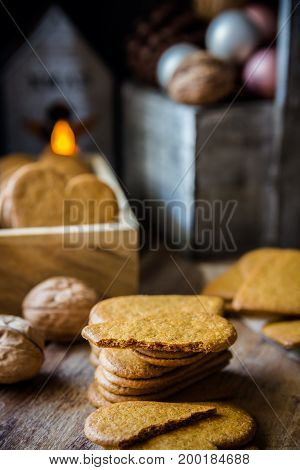 Stack of whole and broken Christmas gingerbread cookies in wood box lit candle pine cones and colorful baubles rustic kitchen interior festive