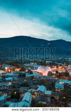 Gori, Shida Kartli Region, Georgia. Cityscape In Bright Yellow Evening Illumination Under Blue Sky In Autumn Twilight. Justice House In Night City. Travel Destination
