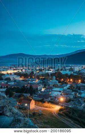 Gori, Shida Kartli Region, Georgia. Cityscape In Bright Yellow Evening Illumination Under Blue Sky In Autumn Twilight. Aerial View Of City. Travel Destination