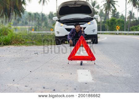 Stressed man sitting after a car breakdown at the side of the road