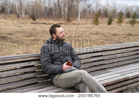 Young man sitting on a bench with a smartphone in his hands outdoors in the park on a cloudy spring day.