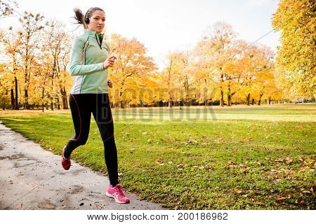 Young woman with headphones running in autumn nature and listening music