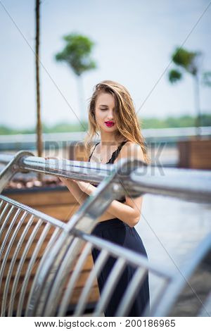 Young beauty girl posing on street near the beautiful handrails