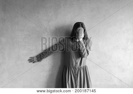 Sad woman standing beside the grunge wall. She is covering her face with a hand. Black and white retouched image.