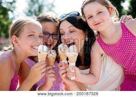 Happy mother and three daughters eating ice cream in summer day