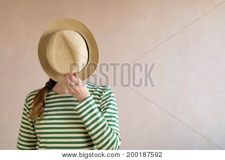 Young woman in a sailor's striped vest covering her face with a straw hat. Picture taken with a natural light.