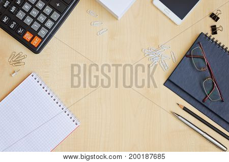 Top view office desk with notepads phone paper for notes calculator glasses. Top view flat lay overhead
