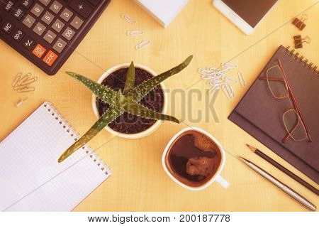 Top view office desk with notepads phone paper for notes calculator glasses and cup for coffee. Toned