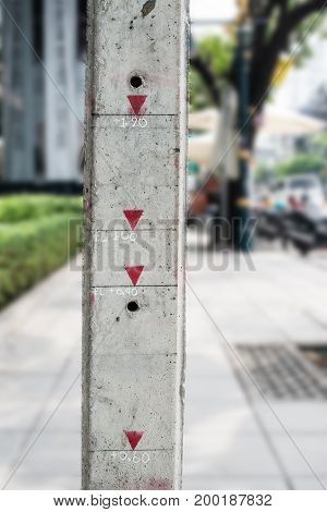 Measuring Concrete Pole With Meter Indication On Footpath Along The Street.