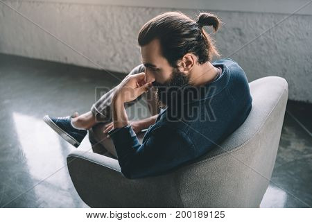 view of thoughtful young businessman sitting in armchair