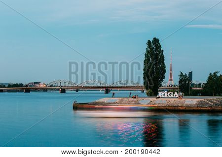 Riga, Latvia. The Concrete Embankment At Daugava River With City Name Sign And Resting People Around. Radio TV Tower, Stone And Railway Bridges Background In Summer Evening Dusk.