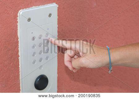 a Close-up of person using building intercom
