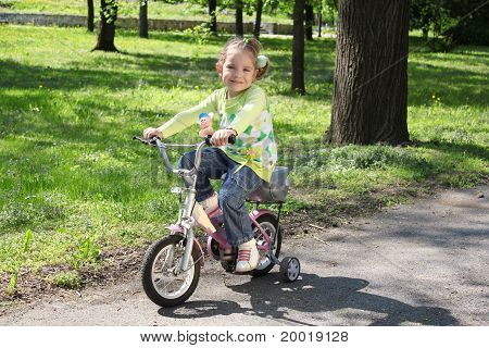 young girl riding bicycle in park