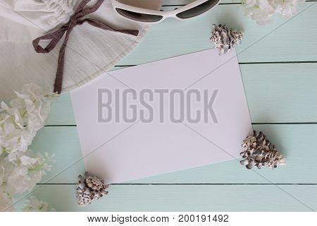 beach accessories on light blue turqoise wooden board. seashells hat and glasses some flowers. Blank sheet of paper for copy space.