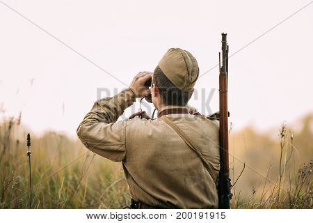 Reenactor Man Dressed As Russian Soviet Red Army Infantry Soldier Of World War II Looking At Old Army Military Binoculars In Meadow At Historical Reenactment