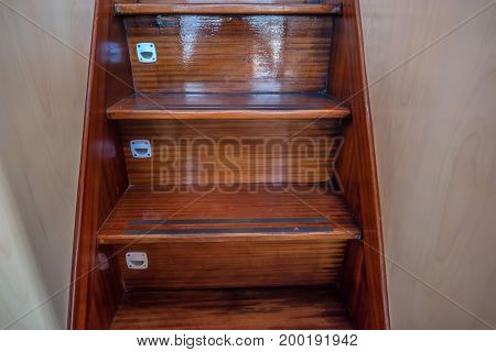 Close up picture of new brown wooden staircase on yacht