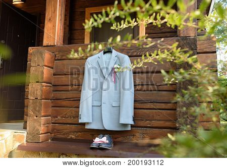 Stylish Elegant Wedding Groom Suit With Boutonniere Hanging On Wooden House Outdoors In Sunny Day. G