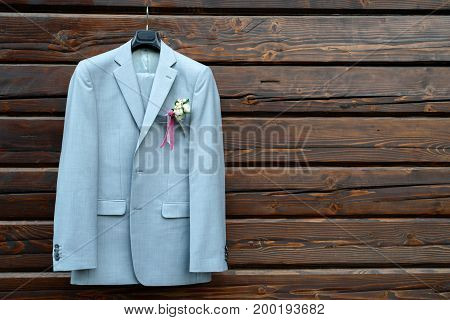 Stylish Elegant Wedding Groom Suit With Boutonniere Hanging On Wooden Background With Copy Space. Gr