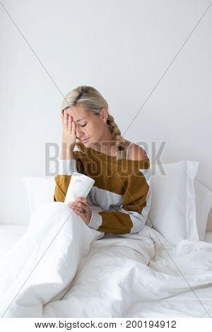 Portrait of ill young Caucasian woman wearing sweater sitting on bed under blanket holding cup and touching fevered forehead