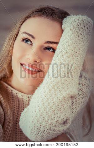 Beautiful caucasian woman is sitting on wooden floor.