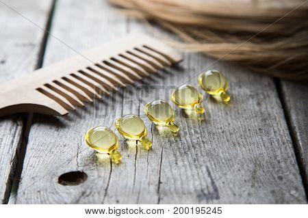 Hair Nurishment. Vitamin Serum Capsule On Wooden Background