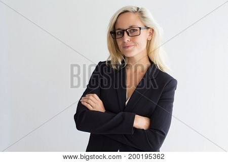 Portrait of confident young Caucasian businesswoman wearing costume and eyeglasses standing with crossed arms and looking at camera