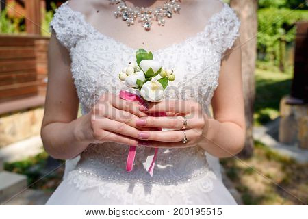 Close Up Bride's Hands  Holding Wedding Boutonniere For The Groom. Beautiful Bride In White Dress Ho