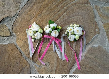 Top view of wedding boutonniere for the groom and bridesmaids on stone background free space. Wedding details outdoor with copy space. Wedding morning preparation