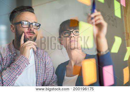 Business people meeting at office and use post it notes to share idea. Brainstorming concept. Sticky note on glass wall.