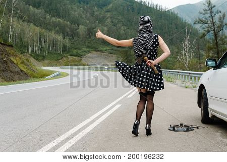 Pin-up Woman On The Road With An Ax Behind Her.
