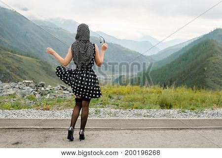 Pin Up Pose Of A Young Woman On A Background Of Mountains.