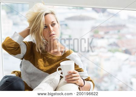 Portrait of thoughtful young Caucasian woman wearing sweater sitting at home holding tea cup and tousling hair