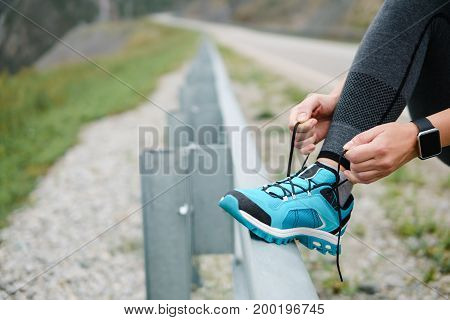Woman lacing running shoes before workout. Marathon.