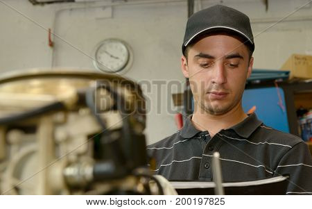 a young mechanic checking the small boat engine