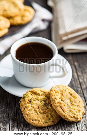 Sweet pistachio cookies and coffee mug on old wooden table.