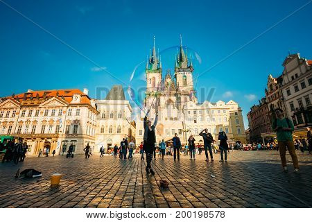 PRAGUE, CZECH REPUBLIC - OCTOBER 15, 2014: Unidentified young woman makes soap bubbles in Old Town Square Staromestske namesti in Prague, Czech Republic