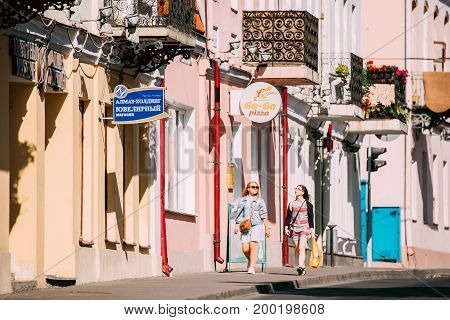 Grodno, Belarus - June 11, 2017: Two Young Women Walking Near Facades Of Old Traditional Houses In Karl Marx Street At Sunny Summer Day In Hrodna, Belarus