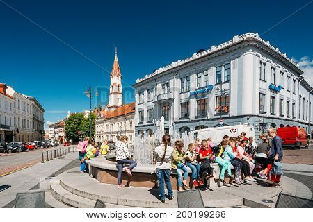 Vilnius, Lithuania - July 5, 2016: Children Resting Near Town Hall Square Fountain In Rotuses Square In Old Town. St. Nicholas Church In Sunny Summer Day. Popular Touristic place
