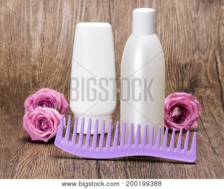 Hair care and styling cosmetics. Hair beauty products and comb with roses on wooden surface