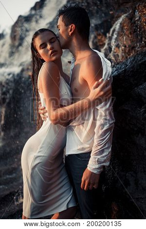 Young enamored wet couple stands on rock and hugs under spray and drops of waterfall. Around them are visible jets and streams of running water.