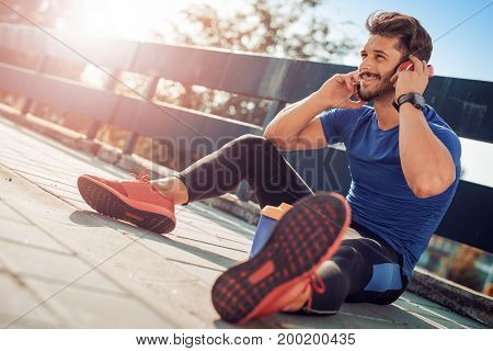 Male runner doing stretching exercise preparing for morning workout outdoors.
