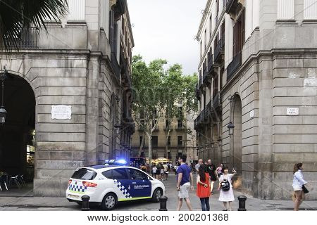 Barcelona, Spain - July 23 2017: Police car patrolling at Royal Square. Guardia Urbana police by Placa Reial filled with tourists in the Gothic Quarter Barri Gotic next to La Rambla.