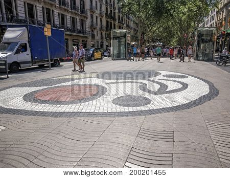 Barcelona, Spain - July 24 2017:Juan Miro mosaic with crowd on La Rambla area. Cirqular mosaic on the pedestrian zone of Las Ramblas at the Plaza de la Boqueria market area.