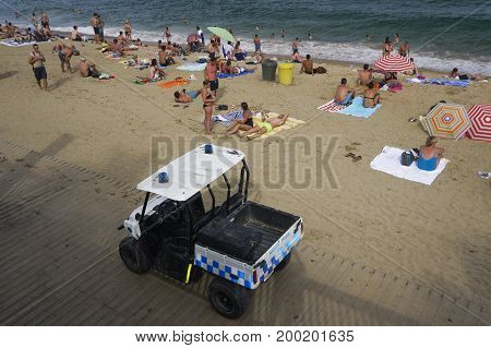 Barcelona, Spain - July 19 2017: Barcelona Police patrol at Barceloneta beach.  Police car securing beach safety patrolling by the sandy crowed beach of Barcelona.