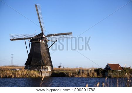 The old Dutch windmills, Holland, rural expanses . Windmills, the symbol of Holland. Holland windmill on a canal. Old mill chalk and flour .