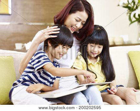 young asian mother and children sitting on couch at home reading a book together happy and smiling.